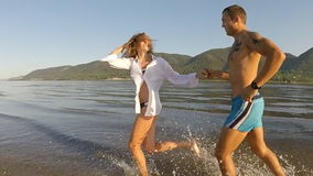 A girl and a guy running around on the beach stock video