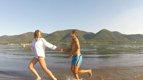 A girl and a guy running around on the beach stock footage
