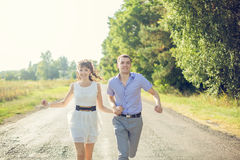 Girl with a guy running down the road Stock Images