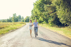 Girl with a guy running down the road Royalty Free Stock Photos