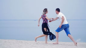 Girl and the guy running on the sand near the sea - love playing fun games.  stock footage