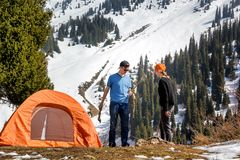 Girl and a guy set up a tourist tent on a grassy lawn against the backdrop of a snow-covered forest on a sunny day. Leisure. Tourism. Healthy lifestyle Stock Image