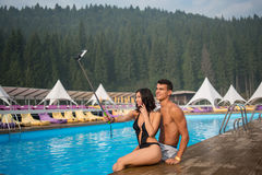 Girl and guy sitting on the edge of swimming pool at the resort and making selfie photo on the phone with selfie stick Stock Photos