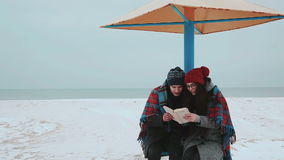 A girl and a guy sitting under a beach canopy, covered with a blanket, reading a book. A girl and a guy on winter beach, covered with a blanket, read a book stock video footage