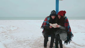 A girl and a guy sitting under a beach canopy, covered with a plaid, reading a book. A girl and a guy on winter beach, read a book and kisses stock footage