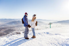 The girl and the guy in the ski resort. Girl and guy in masks for snowboarders holding hands on the background of the ski slopes Stock Photo