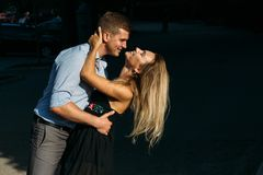 The girl and the guy are smiling, bending over, the guy wants to kiss the girl. the sun shines on their faces. pair on a dark. Background,shot with hard light stock image