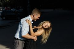 The girl and the guy are smiling, bending over, the guy wants to kiss the girl. the sun shines on their faces. pair on a dark. Background,shot with hard light royalty free stock photo