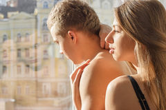 Girl and the guy are standing next to the window Stock Photography