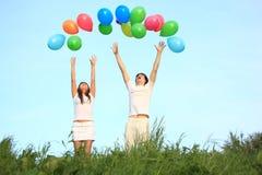 Girl and  guy start balloons in sky Stock Photo