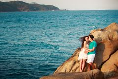 girl and guy on stone against sea Royalty Free Stock Photo