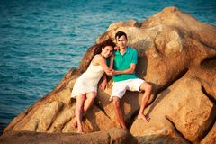 girl and guy on stone against sea Royalty Free Stock Photos