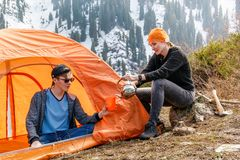 Girl and a guy at a stop with a tourist tent drinking tea or coffee on a background of forest snow-capped mountains Stock Photography