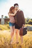 Girl and guy with a suitcase outdoors Stock Photo