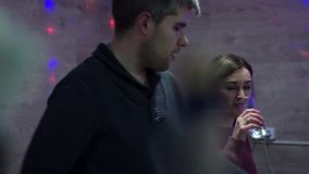 Girl with a guy swear at a party. The girl is drinking pills. The guy proves his position. stock video footage