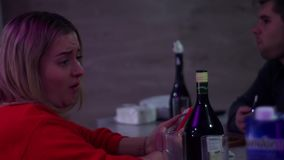 The girl and the guy swear. Private party. Girl in red displeased. stock video