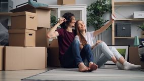 Girl and guy taking selfie with keys in new house using modern smartphone camera. Girl and guy are taking selfie with keys in new house using modern smartphone stock video