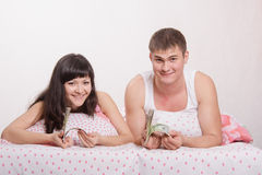 Girl and guy with a wad of dollars in bed Stock Images