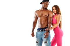 Young fitenss athletic woman in a beautiful pink sportswear, against black athlet bodybuilder man on white background. Copyspace f. The girl in the gym in a stock photo