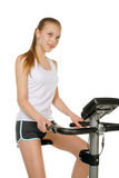 Girl with gym bicycle Stock Images