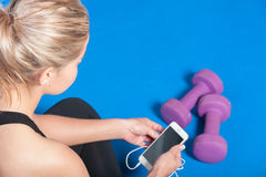 Girl at the gym checking her phone Stock Photography