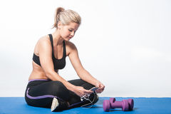 Girl at the gym checking her phone Royalty Free Stock Images
