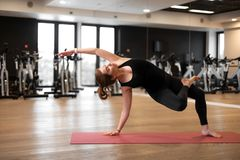 The girl in the gym does yoga to keep herself in shape or control excess weight.  royalty free stock photography