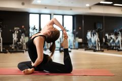 The girl in the gym does yoga to keep herself in shape or control excess weight.  royalty free stock photo