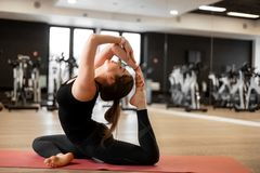 The girl in the gym does yoga to keep herself in shape or control excess weight.  stock photos