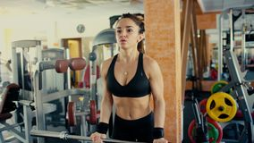 Young sporty woman brunette with long hair lifting barbell bar in gym. 4 k
