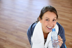 Girl in gym drinking water. Girl sitting in gym with bottle of water Royalty Free Stock Image