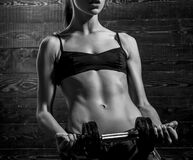 Girl gym dumbbells. Fitness model doing intense training. Woman working out with dumbbells on dark wooden background