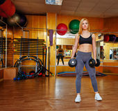 Girl in gym with dumbbells Royalty Free Stock Photo
