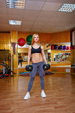 Girl in gym with dumbbells Stock Images