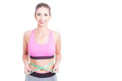 Girl at gym holding centimeter around waist Royalty Free Stock Image