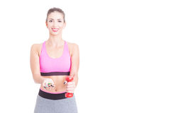 Girl at gym holding pills and dumbbell Stock Images