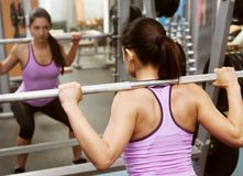 Girl gym lifts bar in front mirror royalty free stock photo