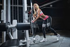 Young beautiful blonde girl doing exercises in the gym, wearing. A girl in the gym makes exercises for the development of leg muscles using sports equipment Royalty Free Stock Photo