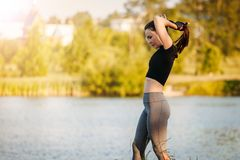 Girl gym in near the lake in city Park. Fitness in nature. Morning exercise with beautiful, sport woman royalty free stock photo