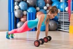 Girl at gym push-up pushup exercise dumbbells. Girl at gym push-up strength pushup exercise with dumbbells workout royalty free stock photos