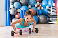 Girl at gym push-up pushup exercise dumbbells Royalty Free Stock Photos