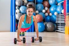 Girl at gym push-up pushup exercise dumbbells Royalty Free Stock Photo