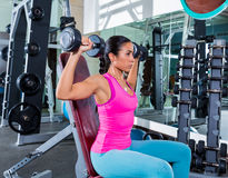Girl at gym seated dumbbell shoulder press Royalty Free Stock Photo