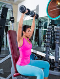 Girl at gym seated dumbbell shoulder press. Workout exercise Stock Photography