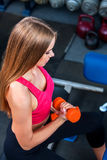 Girl in a gym, shakes  muscles hands. Biceps foreground. Stock Photos