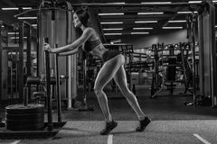 Beautiful brunette, is engaged in a crossfit, in a modern g Royalty Free Stock Photos