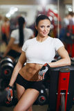 Girl in gym smiling happy standing by fitness machines Stock Image