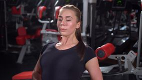 Girl in the gym. Weight training. Work on the muscles of the back. Women working out on rowing machine in gym. Women on stock video footage