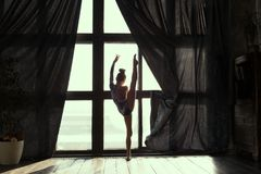 Girl gymnast opened  wake up  and the curtains and doing an exercise in front of the window. In the early morning stock images