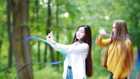 Girl gymnast practicing with a blue ribbon in the park. Girlfriend takes on a mobile phone. Beautiful girl gymnast practicing with a blue ribbon in the park stock video